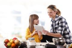 Moder och dotter i kök Arkivbild