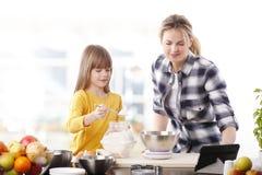 Moder och dotter i kök Fotografering för Bildbyråer