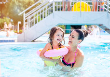 Moder och dotter i simbassängen, aquapark solig sommar royaltyfri bild