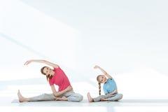 Moder och dotter i sportswear som övar på yogamats arkivfoton