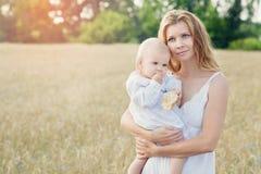 Moder och dotter i vetefält lycklig familj utomhus sunt barn med modern på picknick med bröd och att mjölka i guld- royaltyfria foton