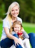 Moder och dotter med äpplesammanträde på gräset royaltyfria bilder