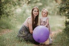 Moder och dotter med ballonger Härlig lycklig moder med dottern som har gyckel i det gröna fältet som rymmer ballonger royaltyfri fotografi