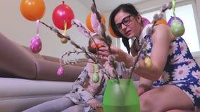 Moder och dotter med dekorativa ägg i rede
