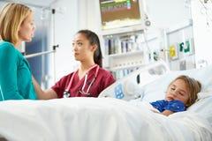 Moder och dotter med den sjuksköterskaIn Intensive Care enheten arkivbild
