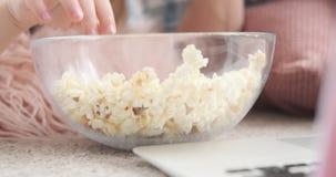 Moder och dotter med en bunke av popcorn