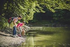 Moder och dotter med hunden vid sjön royaltyfri bild