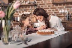 Moder och dotter med kakan på tabellen, begrepp för ferie för dag för moder` s fotografering för bildbyråer