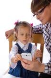 Moder och dotter med mobiltelefonen Fotografering för Bildbyråer