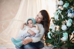 Moder och dotter nära en julgran, ferie, gåva, dekor, nytt år, jul, livsstil Arkivbild