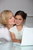 Moder och dotter på bärbara datorn Royaltyfri Fotografi