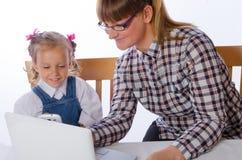 Moder och dotter på datoren Royaltyfri Fotografi