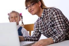 Moder och dotter på datoren Royaltyfria Bilder
