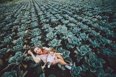 Moder och dotter på fältet med kål Arkivfoto
