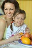Moder och dotter som äter frukter Arkivbild