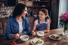 Moder och dotter som äter havreflingor arkivfoton