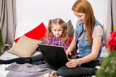 Moder och dotter som använder bärbara datorn på säng i sovrum Mamman visar information om dotter på bärbar datorskärm royaltyfri foto
