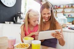 Moder och dotter som använder den Digital minnestavlan på frukosttabellen arkivbild