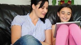 Moder och dotter som använder minnestavladatoren arkivfilmer
