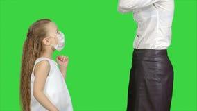 Moder och dotter som bär kirurgiska maskeringar för att skydda från en epidemi på en grön skärm, chromatangent lager videofilmer