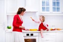 Moder och dotter som bakar en paj Fotografering för Bildbyråer