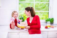 Moder och dotter som bakar en paj Royaltyfri Fotografi