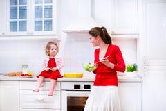 Moder och dotter som bakar en paj Arkivbilder
