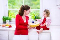 Moder och dotter som bakar en paj Arkivfoto