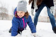 Moder och dotter som bygger en snögubbe i vinternatur Arkivbild