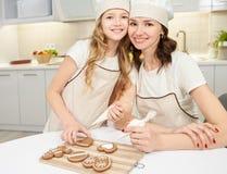 Moder och dotter som dekorerar och att glasa ljust rödbrun kakor fotografering för bildbyråer