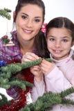 Moder och dotter som dekorerar julgranen Royaltyfria Bilder