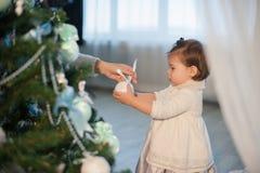 Moder och dotter som dekorerar leksaker för en julgran, ferie, gåva, dekor, nytt år, jul, livsstil Arkivbilder