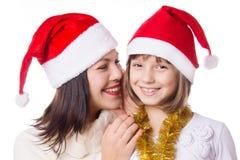 Moder och dotter som delar sig hemligheter på julafton Arkivfoton