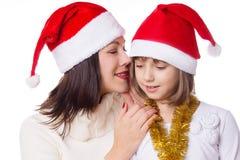 Moder och dotter som delar sig hemligheter på julafton Arkivbild