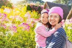 Moder och dotter som framme ler av blomman Royaltyfri Bild