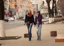 Moder och dotter som går i staden Arkivfoto