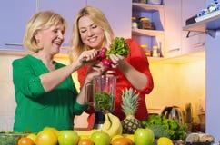 Moder och dotter som gör den sunda drinken Arkivbilder