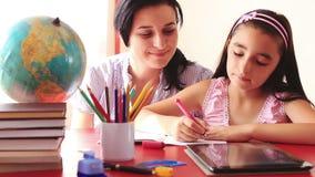 Moder och dotter som gör läxa på den digitala minnestavlan arkivfilmer