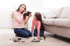 Moder och dotter som gör makeupsammanträde på golvet arkivbilder