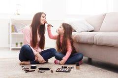 Moder och dotter som gör makeupsammanträde på golvet royaltyfri bild