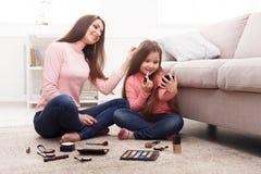 Moder och dotter som gör makeupsammanträde på golvet royaltyfria bilder