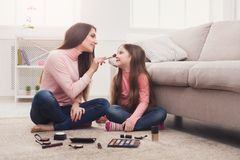 Moder och dotter som gör makeupsammanträde på golvet fotografering för bildbyråer