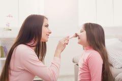 Moder och dotter som gör makeupsammanträde på golvet royaltyfri foto