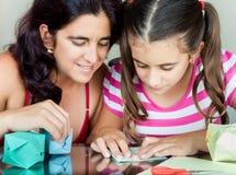 Moder och dotter som gör origami Arkivfoto