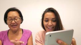 Moder och dotter som gör roliga selfiefoto med den mobila minnestavlan 4K stock video