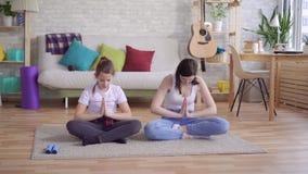 Moder och dotter som gör yoga som sitter på golvet lager videofilmer