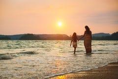 Moder och dotter som g?r p? stranden med solnedg?ng arkivbild