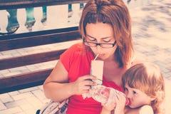 Moder och dotter som har frukosten utomhus Fotografering för Bildbyråer