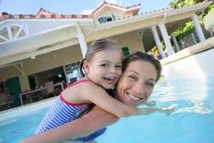 Moder och dotter som har gyckel i en simbassäng Arkivbild