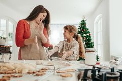 Moder och dotter som har gyckel, medan göra julkakor Royaltyfri Foto